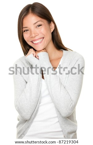 Mixed race Chinese Asian / Caucasian young woman with cute adorable playful shy smile. Model wearing grey cardigan isolated on white background.