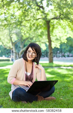 Mixed race college student sitting on the grass working on laptop at campus - stock photo