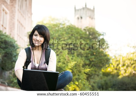 Mixed race college student working on laptop at campus