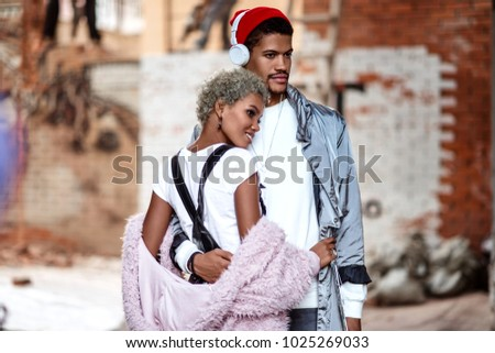 Mixed race confident stylish male wears headphones, embraces his black girlfriend, pose together against brick wall with thoughtful expression, enjoy spare time. African American couple in love. #1025269033