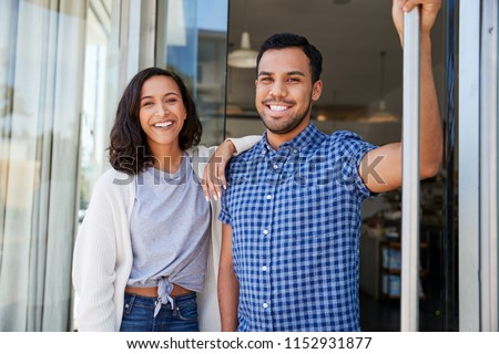Mixed race couple outside the coffee shop they own