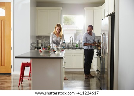 Mixed race couple preparing a meal in their kitchen