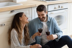Mixed race couple sit on floor drink red wine relieving fatigue at moving day, celebrate relocation to own house. Romantic dating, kitchen renovation services ad, relations, housewarming event concept