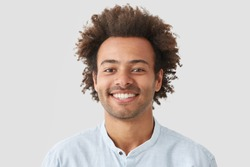 Mixed race curly male with broad smile, shows perfect teeth, being amused by interesting talk, has bushy curly dark hair stands indoor against white blank wall. Close up of joyful African American man