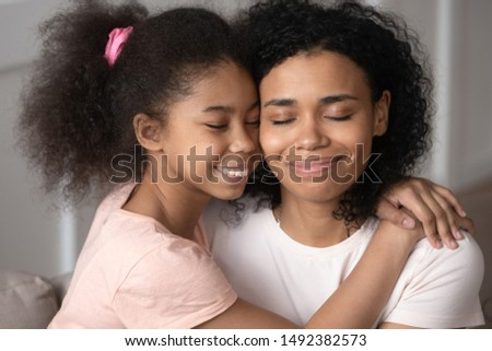 Mixed-race daughter embraces mother people closed eyes enjoy moment of tenderness and caress, adopted child express gratitude to new mom blessed to have family, children the greatest treasure concept #1492382573