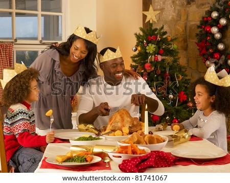 Mixed race family having Christmas dinner