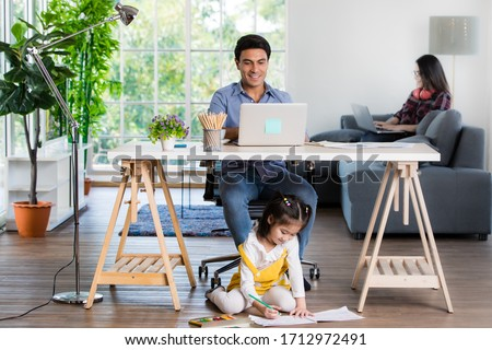 Mixed race family sharing time in living room. Caucasian father using notebook computer to work and half-Thai playing and painting under desk while Asian mother with laptop working her job on sofa. Foto d'archivio ©
