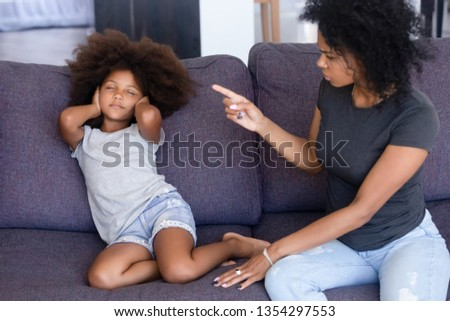 Mixed race family sitting on couch at home mother scold scream at little daughter, kid not listen ignore mom close eyes cover her ears with hands. Complicated relationships and family conflict concept ストックフォト ©