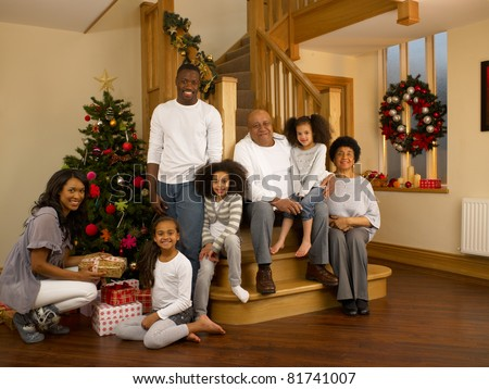 Mixed race family with Christmas tree and gifts - stock photo