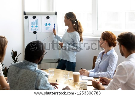 Mixed race female business coach presenting report standing near whiteboard pointing on sales statistic shown on diagram and chart teach diverse company members gathered together in conference room #1253308783