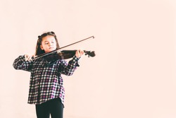 Mixed race female kid playing violin, child education or music concept, with copy space