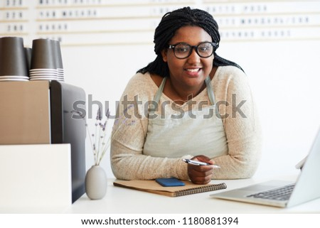 Mixed-race girl in workwear and eyeglasses looking at you while standing by workplace in cafeteria Photo stock ©