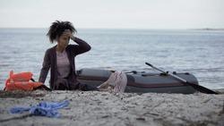 Mixed race girl sitting on beach near boat, flood disaster victim, shipwreck