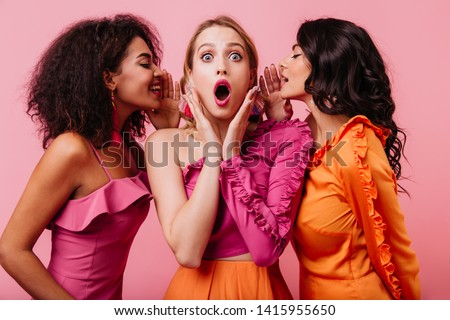 Mixed race girls sharing secrets. Studio photo of three young women talking on pink background.