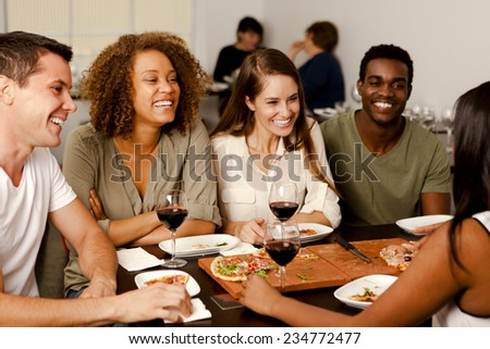 Mixed-race group of friends laughing together in a pizza restaurant