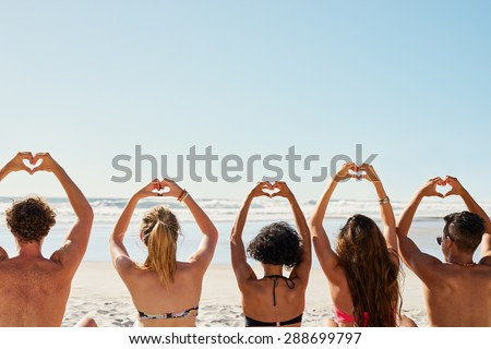 Mixed race group of friends making heart shapes with hands raised up to the sky show a love of summer and sunshine shot from the back #288699797