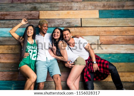 Mixed race group of teenagers having fun on the couch - Multi-ethnic young adults partying at home