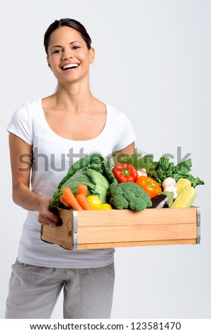 Mixed race happy young woman holding a crate full of fresh organic vegetables on grey background, promoting healthy diet and lifestyle