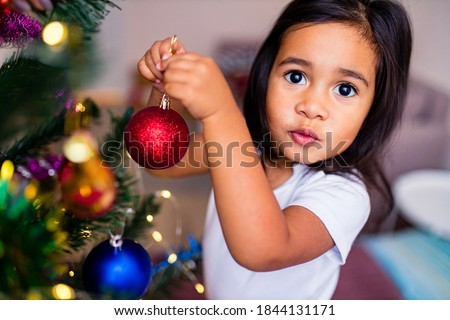 mixed race little cute girl decorating a christmas tree in the xmas morning in bedroom and wishing a wish
