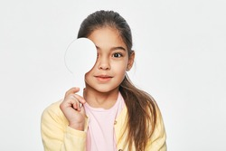 Mixed race little girl having eye exam with one eye covering using a special ophthalmic tool, on a light grey background. Eye test for child