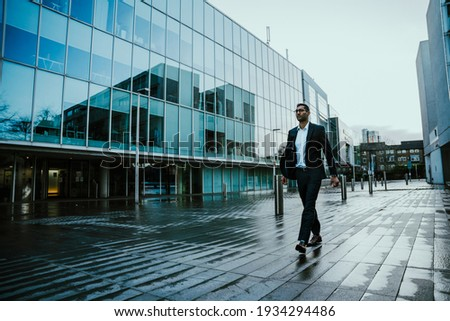 Mixed race male businessman walking eagerly to work through classy office buildings Foto stock ©