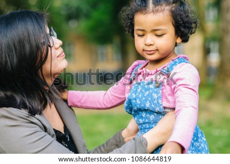 Mixed race mother communicate with her toddler dark-skinned daughter on while walking together in summer park. Education, growing up, psychology behavior concept. #1086644819
