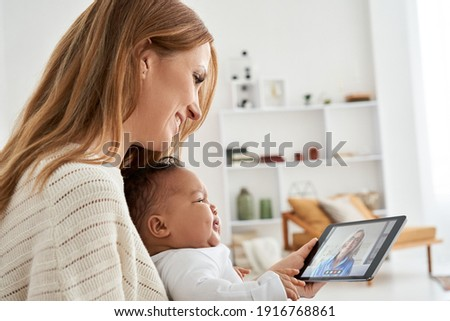 Mixed race parent and child, young caucasian mother holding cute crying african infant baby daughter looking at tablet having virtual distance business or family meeting video call working from home. Stock photo ©