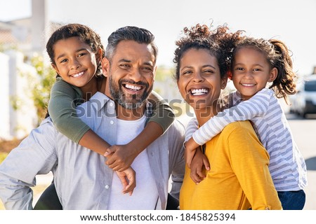Mixed race parents giving piggyback ride to their children. Portrait of happy african mother and indian father with daughters looking at camera. Smiling family standing with their little girls. Foto d'archivio ©