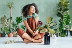 Mixed race playfu woman sitting on floor gardening in home. Growing plants at home. Plant parent concept woman cultivating home plants.