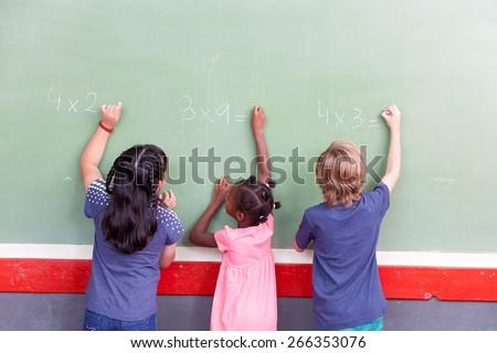 Mixed race school children writing on chalkboard.