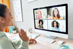 Mixed race teen girl waving talking to happy diverse teenage friends during online virtual chat video call in group conference distance chat virtual meeting using computer at home. Over shoulder view.