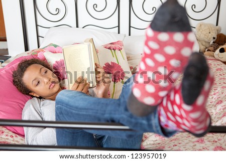 Mixed race teenage girl reading a book while laying down on her bed at home.