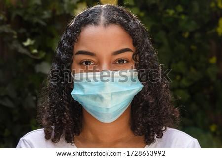 Mixed race teenager teen girl young woman wearing a face mask during the Coronavirus COVID-19 virus pandemic