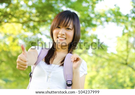 Mixed race thumb up college girl standing at campus