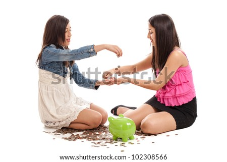 Mixed race tween and teen girls counting money in their piggy bank isolated on white background