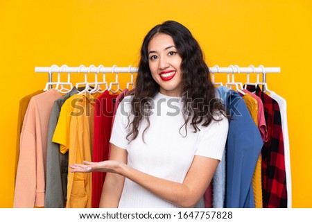Mixed race woman in a clothing store extending hands to the side for inviting to come Foto d'archivio ©