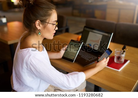 Mixed race woman in glasses working with multiple electronic internet devices. Freelancer businesswoman has tablet and cellphone in hands and laptop on table with charts on screen. Multitasking theme #1193280682