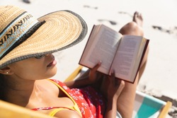 Mixed race woman on beach holiday sitting in deckchair reading book. healthy outdoor leisure time by the sea.