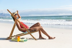Mixed race woman on beach holiday sitting in deckchair sunbathing. healthy outdoor leisure time by the sea.