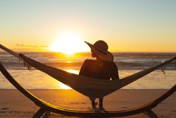 Mixed race woman on beach holiday sitting in hammock during sunset. healthy outdoor leisure time by the sea.