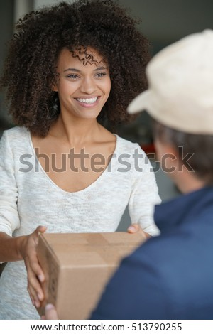 Mixed race woman receiving package from delivery man