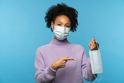 Mixed race woman wear anti virus protection face mask to prevent from coronavirus, Covid-19, reminds of the mandatory wearing in public places,  showing finger at the mask, isolated on blue background