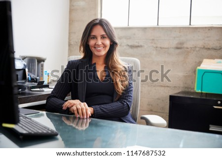 Mixed race woman with long hair sitting at desk in office #1147687532