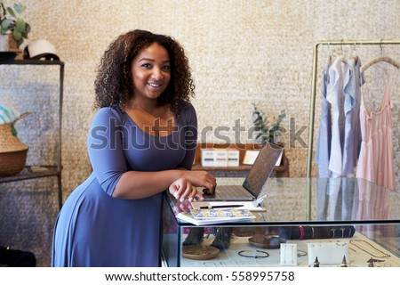 Mixed race woman working in clothes shop looking to camera #558995758