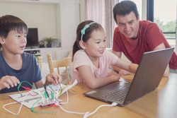 Mixed race young Asian children learning coding with father, remote learning  at home, STEM science, homeschooling education, Social distancing, isolation concept