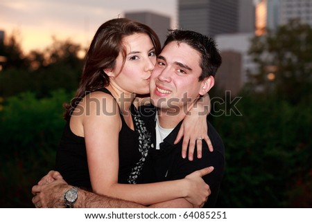 Mixed race young couple in an affectionate embrace at sunset in an outdoor park setting with downtown in the background.