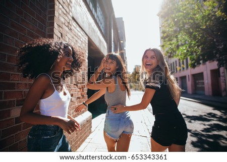 Mixed raced group of friends walking together in city. Three young people having fun outdoors on road. #653343361