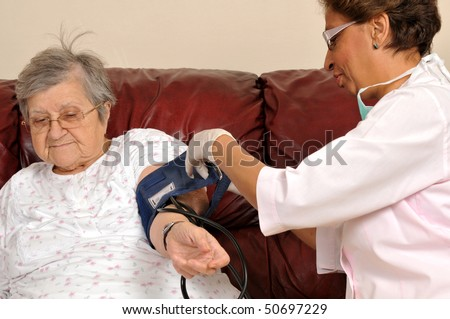 Mixed raced nurse measuring senior patient's blood pressure - series of MEDICAL IMAGES.