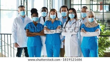 Mixed-races busy team of male and female doctors posing to camera and crossing hands in hospital. International group of medics in medical masks. Protected multi ethnic physicians and nurses in clinic Foto d'archivio ©
