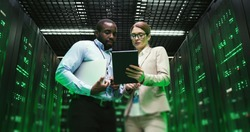Mixed-races man and woman with tablet device discussing issue at datacenter. Multiethnic developers standing at servers storage and looking at gadget. Male and female analytics colleagues talking.